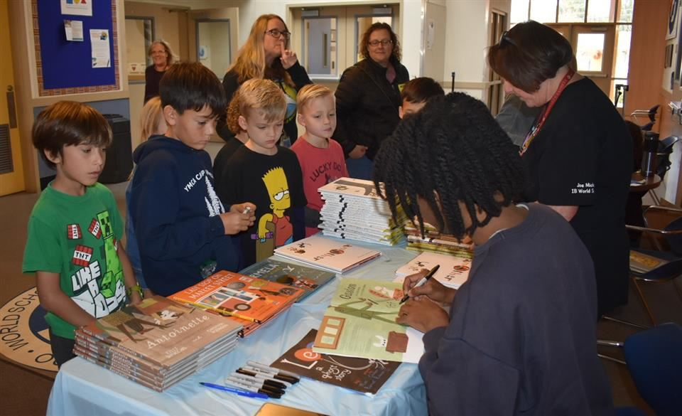 Robinson signing books for students