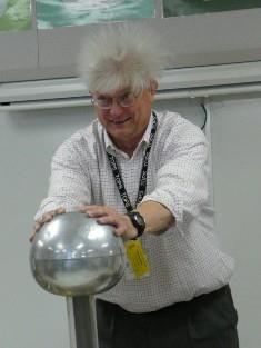 scientist with his hair sticking up while touching a Van de Graaf generator